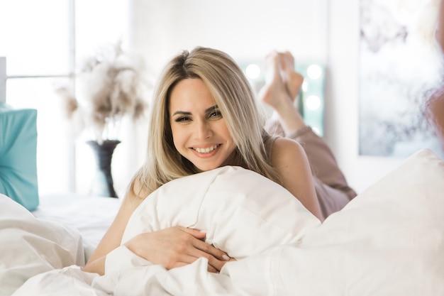 Fille blonde serrant un oreiller sur son lit à l'intérieur