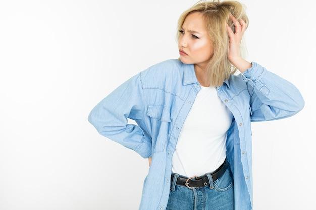 Fille blonde sexy d'une manière élégante avec une chemise en coton se faisant passer pour un modèle sur un fond isolé blanc