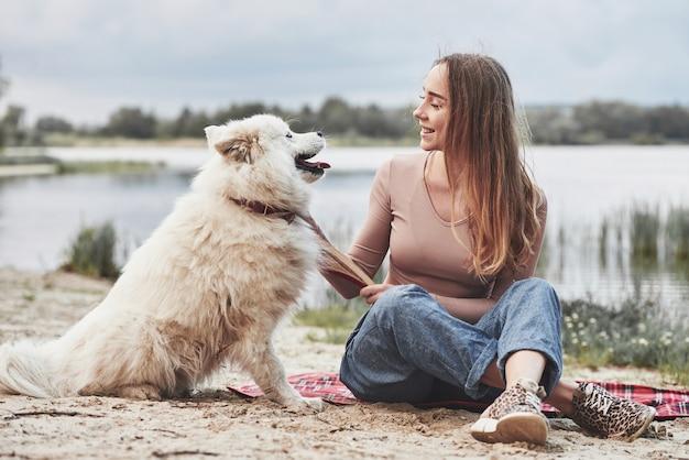 Une fille blonde avec son mignon chien blanc passe un bon moment sur une plage.