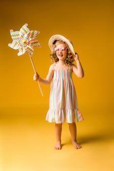 Fille blonde souriante à lunettes de soleil et robe d'été tenant un moulin à vent