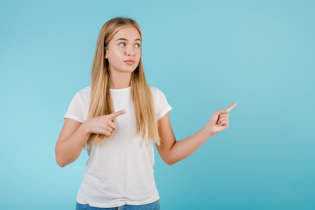 Fille blonde souriante positive, pointant les doigts sur la surface isolée sur bleu