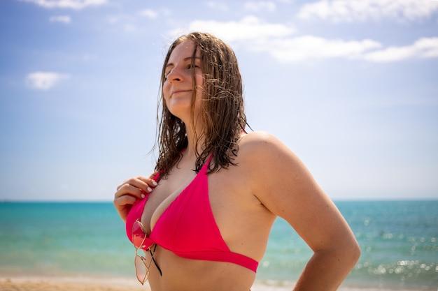 Fille blonde souriante et regardant la caméra de manière ludique, vêtue d'un bikini rose et de coeurs de lunettes.