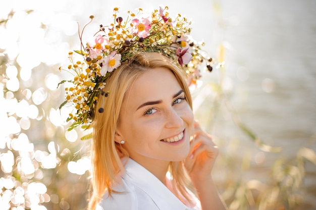 Fille blonde souriante romantique dans une gerbe de fleurs