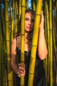 Fille blonde de style de vie de race blanche dans une robe noire glamour dans le parc dans la nature perchée sur de beaux bambous profitant des beautés de la nature