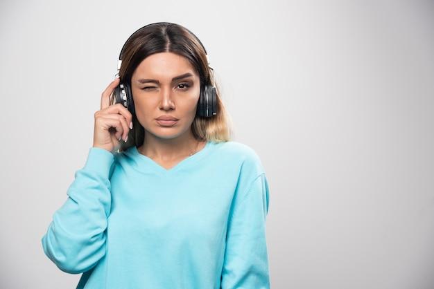 Fille blonde en sweat-shirt bleu portant des écouteurs et essayant de comprendre la musique