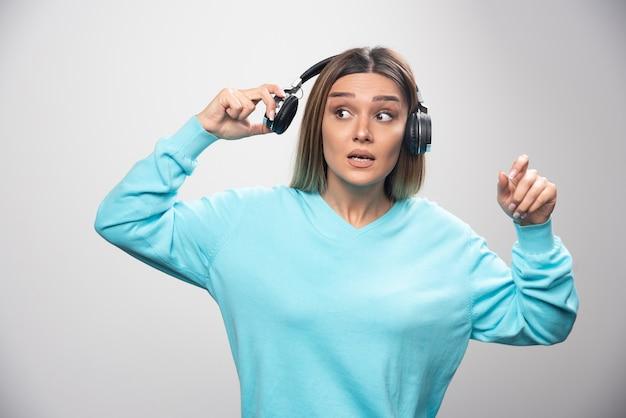 Fille blonde en sweat-shirt bleu sortant les écouteurs pour entendre les gens autour.