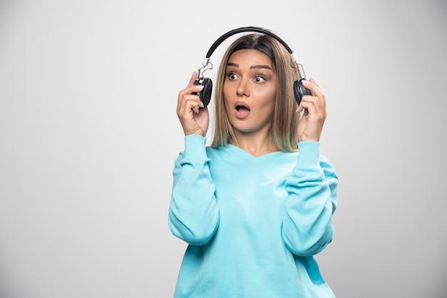 Fille blonde en sweat-shirt bleu sortant les écouteurs pour entendre les gens autour