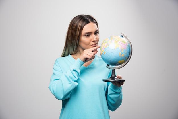 Fille blonde en sweat-shirt bleu tenant un globe, deviner l'emplacement et s'amuser.