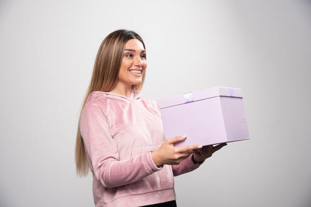 Une fille blonde en sweat-shirt a reçu un coffret cadeau et se sent positivement surprise