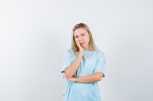 Fille blonde en t-shirt bleu penchée sur la joue sur la paume, tenant la main sous le coude et à la jolie vue de face.