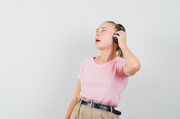 Fille blonde en t-shirt, pantalon, écouter de la musique avec des écouteurs et à la vue ravie, de face.