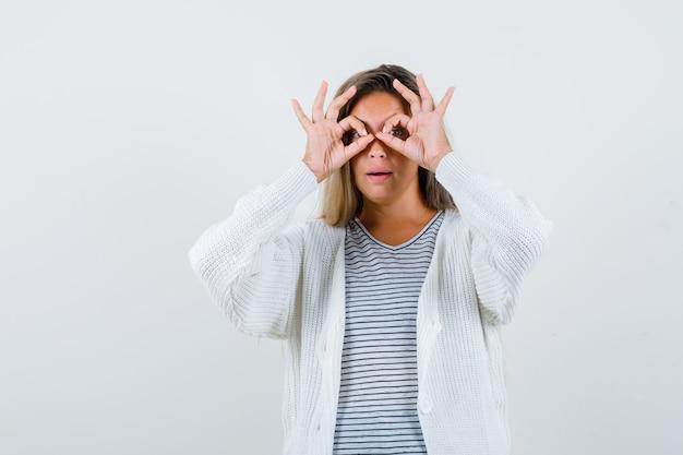 Fille blonde en t-shirt rayé, cardigan blanc et pantalon en jean montrant le geste des jumelles et à la vue amusée, de face.