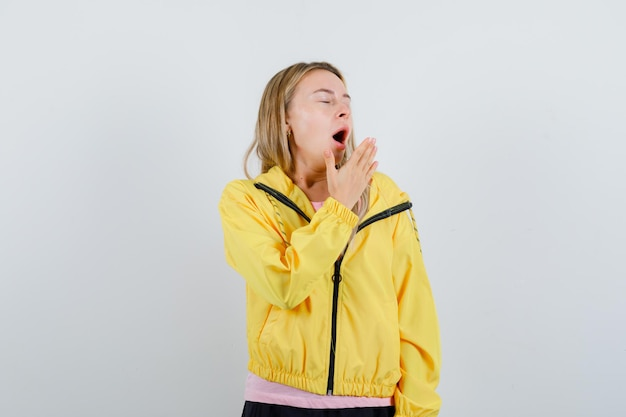 Fille blonde en t-shirt rose et veste jaune tenant la main près de la bouche, bâillant et ayant l'air endormi