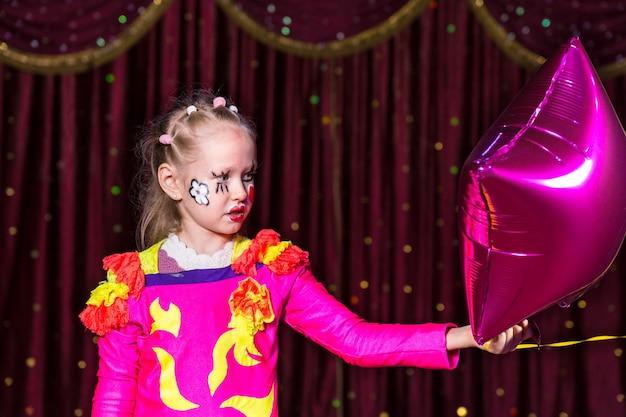 Fille blonde talentueuse jouant avec un diadème coloré et des fleurs peintes sur le visage et cousues sur un costume de théâtre rose vif
