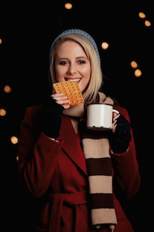 Fille blonde avec une tasse de café et une gaufre