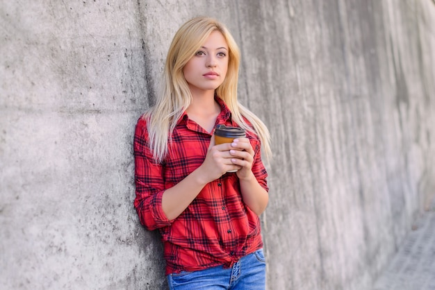 Fille blonde avec une tasse dans les mains fond de mur gris