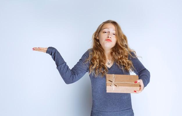 Fille blonde tenant une boîte-cadeau en carton et semble confuse et réfléchie.