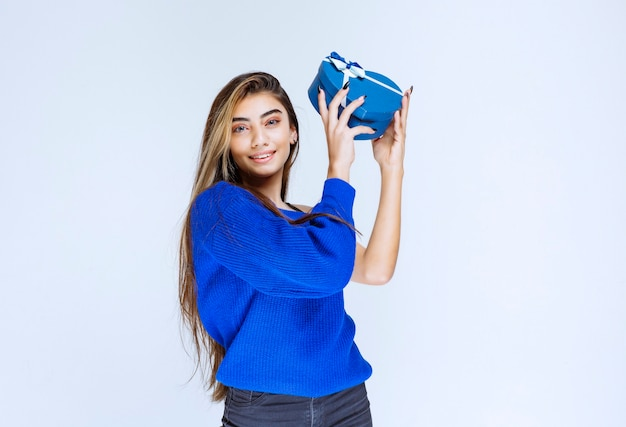Fille Blonde Tenant Une Boîte-cadeau En Forme De Coeur Bleu. Photo gratuit