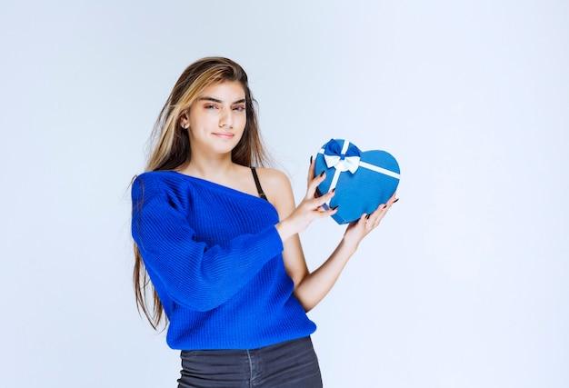 Fille blonde tenant une boîte-cadeau en forme de coeur bleu.