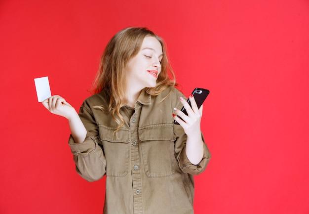 Fille blonde tenant une carte de visite et parlant au téléphone.