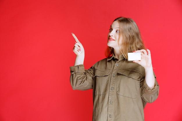 Fille blonde tenant une carte de visite et pointant vers son collègue.