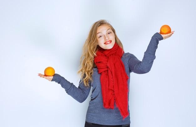 Fille blonde tenant deux oranges dans les deux mains.