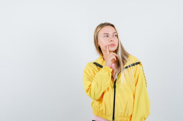 Fille blonde tenant le doigt près de la bouche en veste jaune et regardant pensive