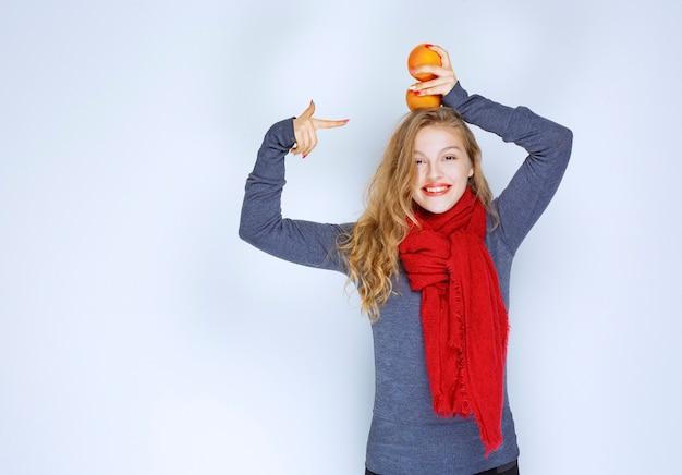 Fille blonde tenant des fruits orange au-dessus de sa tête.
