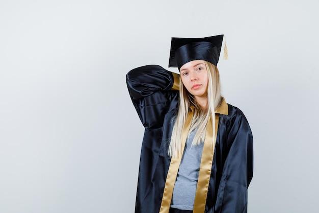 Fille blonde tenant la main sur le cou en uniforme de diplômé et à la mignonne