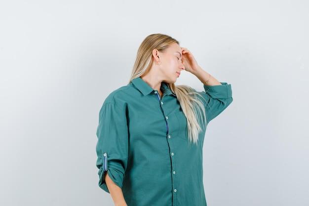 Fille blonde tenant la main sur le front, ayant des maux de tête en blouse verte et l'air ennuyé.
