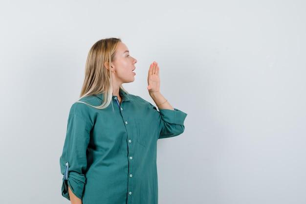 Fille blonde tenant la main près de la bouche comme appelant quelqu'un en blouse verte et à l'accent