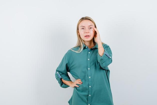 Fille blonde tenant la main sur la taille tout en mettant la main sur la joue en blouse verte et l'air sérieux.