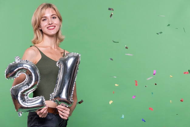 Fille blonde tenant une pancarte de 21 ballons