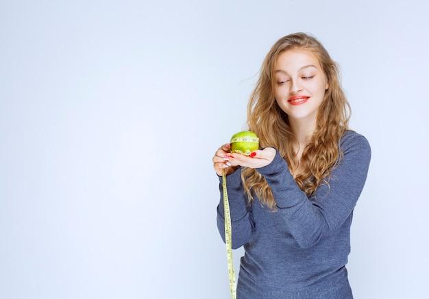 Fille blonde tenant une pomme verte dans ses paumes.
