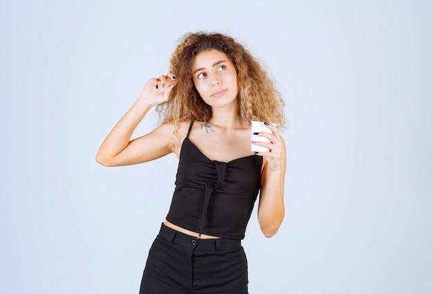 Fille blonde tenant une tasse de café et pensant.