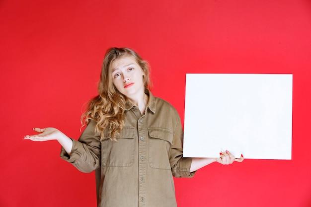 Fille blonde tenant une toile et semble insatisfaite.
