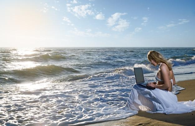 Fille blonde utilisant un ordinateur portable sur la plage de la mer