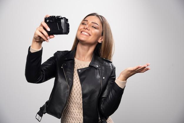 Fille blonde en veste de cuir noir prenant ses selfies avec un appareil photo.