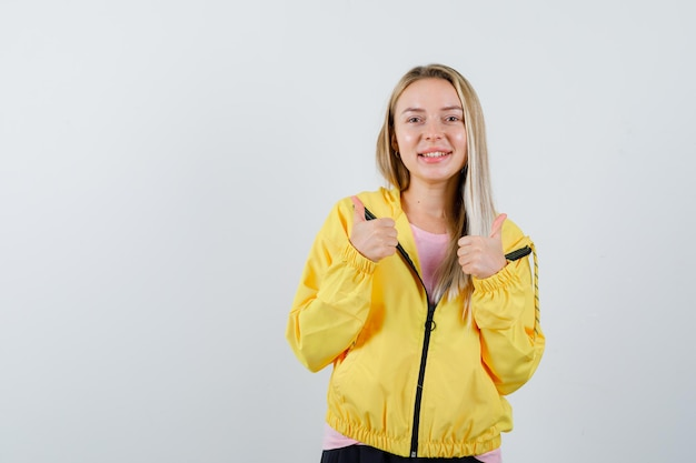 Fille blonde en veste jaune montrant double pouce vers le haut et à heureux