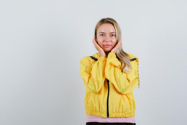 Fille blonde en veste jaune se tenant la main près des joues et à la délicatesse