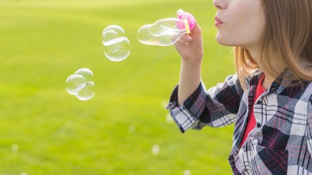 Fille blonde vue de côté faisant des bulles de savon