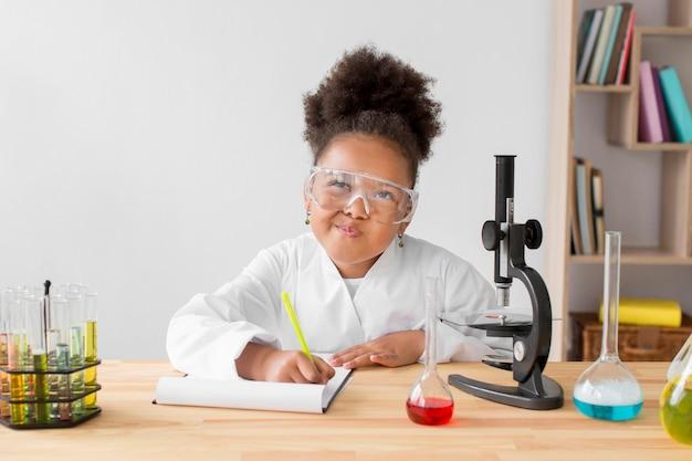 Fille en blouse de laboratoire et lunettes de sécurité écrit dans le bloc-notes