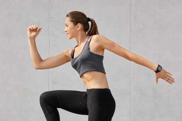 Fille de bodybuilder active photographiée en mouvement, a une queue de cheval sombre, fait des exercices d'étirement vêtus de vêtements décontractés, pose sur gris. gymnaste féminine a des objectifs de fitness