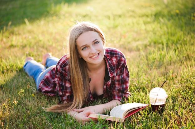 Fille boire du jus et lire un livre dans un parc.