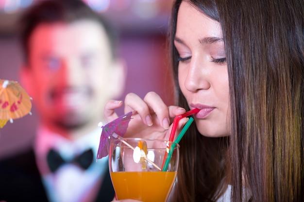 La fille boit un délicieux cocktail au bar.