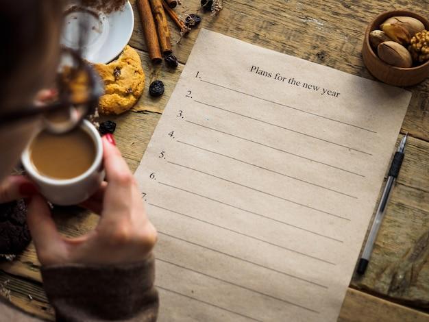La fille boit du café et fait des plans pour la nouvelle année.