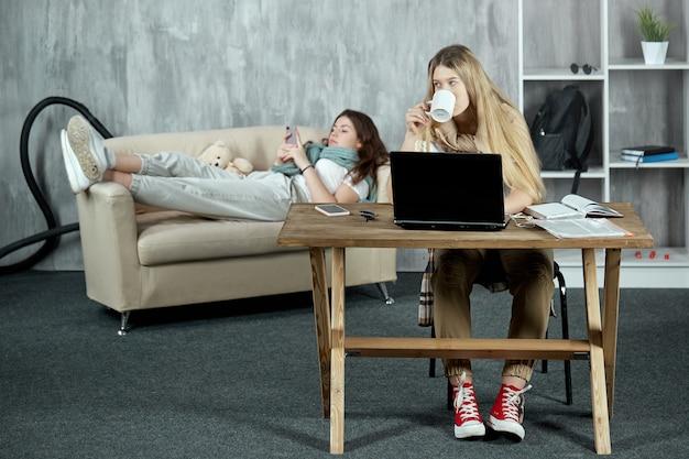 La fille boit du thé entre les conférences en ligne sur un ordinateur portable et son amie se repose sur le canapé