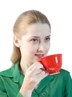 Fille boit du thé à partir d'une tasse rouge