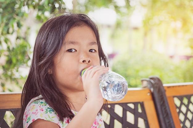 Fille boit de l'eau d'une bouteille