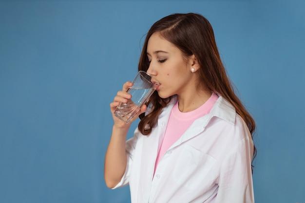 Fille boit de l'eau claire dans un verre